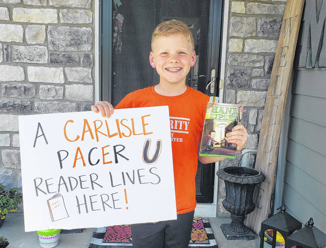 "Carlisle Elementary School third grader Brad Masters holds his Right to Read Week sign and a book. Students at Carlisle were asked to read for 20 minutes each day with their families and make a sign for their window or yard saying ""A Carlisle Reader lives here."""