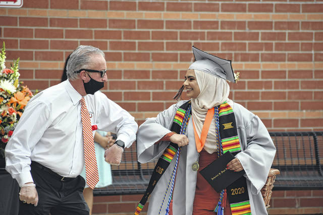 Basma Abdulghafoor gives an elbow bump to Hayes Principal Ric Stranges after receiving her diploma during Saturday's drive-thru graduation ceremony held at Hayes High School.