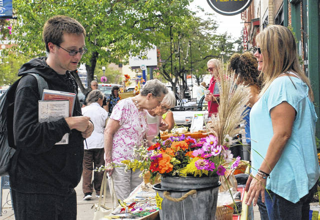 Barbara Reiner, right, touts the quality of her autumnal goodies to a customer in this file photo taken in downtown Delaware in October 2017. Main Street Delaware's Farmers Market is temporarily moving from downtown to the Delaware County Fairgrounds.