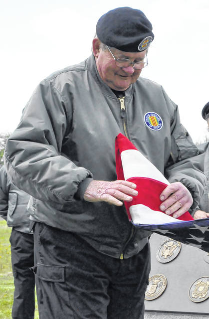 Jim Crosbie folds an American flag during the ceremony.