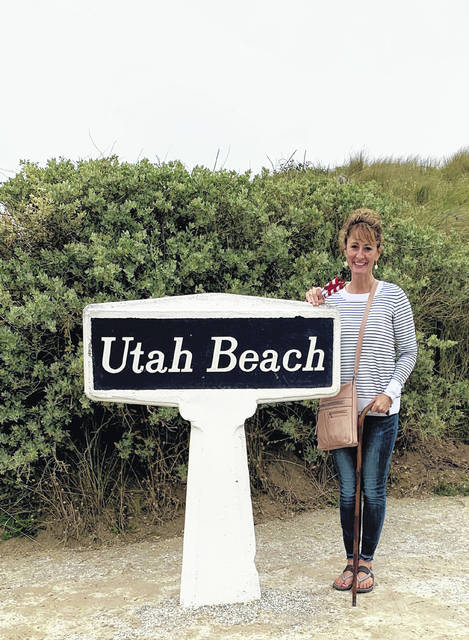 "Beth Rieman, author of ""Unpacking Yesterday: A Brotherhood's Legacy,"" poses on Utah Beach in France with a cane that once belonged to Teddy Roosevelt Jr. The cane was given to her great-uncle during the Normandy invasion."