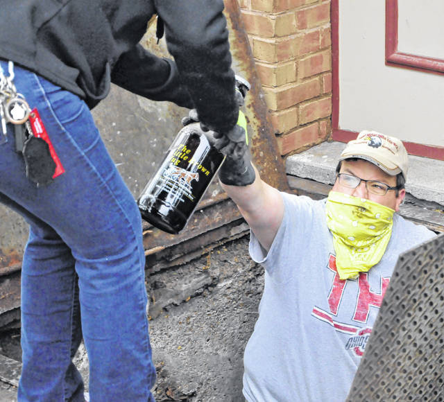 Craig Myers hands up a beer bottle during Wednesday's cleanup efforts at The Backstretch. While many of the salvaged bottles featured well-known brands, this particular bottle depicts The Little Brown Jug.