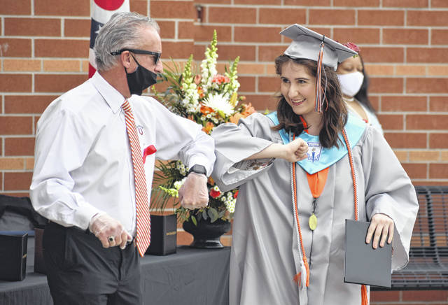 Hayes High School graduate Lizzy Childers elbow bumps with Principal Ric Stranges last month at Hayes' commencement ceremony.