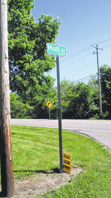 Many yards on Hull Drive have signs requesting drivers slow down.