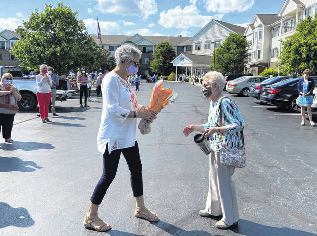 """A Willow Brook employee hands Lu Wellman, right, flowers during Wellman's retirement """"clap out"""" held at Willow Brook at Delaware Run."""