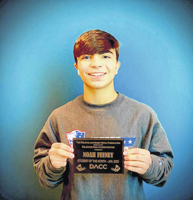 """Recent DACC and Olentangy Liberty High School graduate Noah Feeney poses with a """"student of the month"""" plaque from earlier this year in the DACC welding lab."""