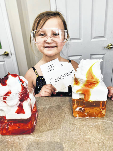 Carlisle Elementary School first grader Sophia Schaffer holds up flash cards at the end of the science experiment she filmed for the MOVA Globes #StayHomeScienceFair competition. In her experiment, Schaffer demonstrates how water passes through a cloud to become rain using food coloring, shaving cream and jars of water.