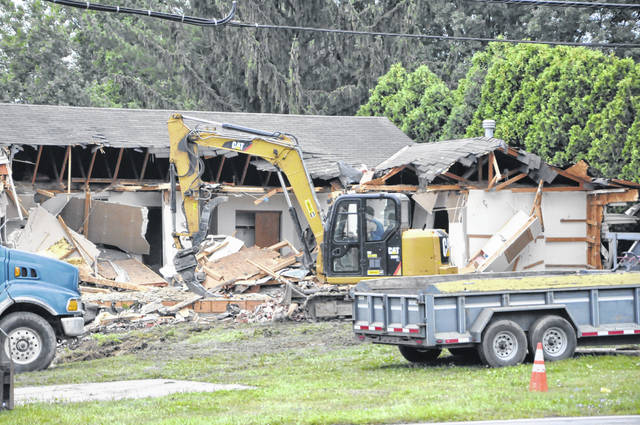 The city-owned duplex at 1271-1273 W. Central Ave. in Delaware has been razed to make room for a nature trail leading down to the Delaware Run. Pictured is a demolition crew hard at work Friday morning.