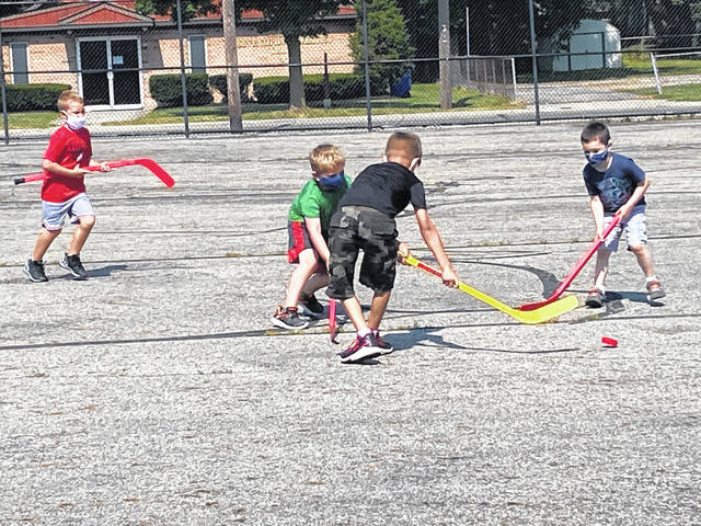 Students in the School Aged Child Care Program at Woodward Elementary School play a game on the playground during the first week of SACC.