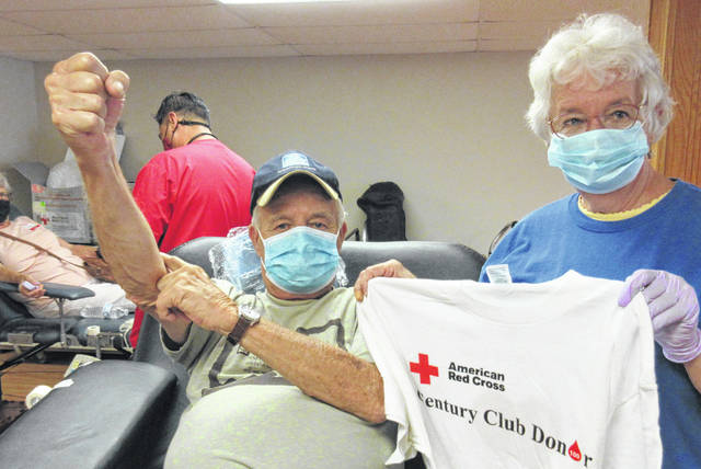 "Polly Horn, coordinator of the Condit blood drives, presents Dave Orndorf with a ""Century Club Donor"" T-shirt from the American Red Cross after giving his 100th pint of blood on Aug. 14."