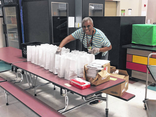 Delaware City Schools employee Joyce Bolton prepares grab and go meals for students in March through the USDA's meal program. The USDA announced recently it's extending the program and offering free lunch and breakfast districtwide to students on school days.