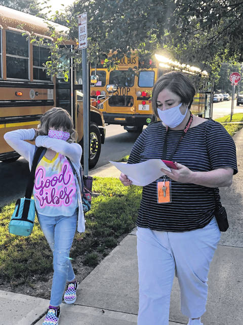 Smith Elementary School Counselor Robin Irion walks a student to the school Monday morning during student arrival. Masks and social distancing are mandatory at all buildings for staff and students this year to prevent the spread of COVID-19.