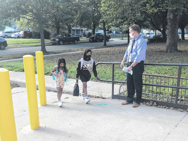 Woodward Elementary School Principal Eric Barr welcomes students to school Friday. Students have been divided into two cohorts based on the first letter of their last name in an effort to reduce class sizes and decrease any possible spread of COVID-19.
