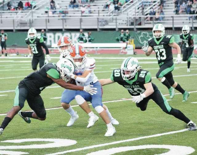 Dublin Coffman's Dorian Weaver and Mitch Broskie (20) converge to tackle Olentangy Orange's Julian DiSabato during the first half of Friday's OCC-Central showdown in Dublin.