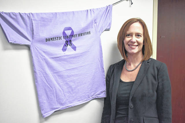 Delaware County Prosecutor Melissa Schiffel stands next to a T-shirt signifying the county's 33rd domestic violence victim this year. Schiffel said there are more than 30 T-shirts hung around the office to raise awareness for domestic violence.