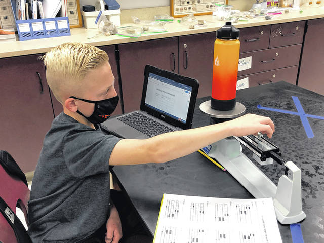 Chase Sims, a sixth grader at Dempsey Middle School, measures his water bottle using a triple beam balance last week in Stephanie Buckingham's science class.