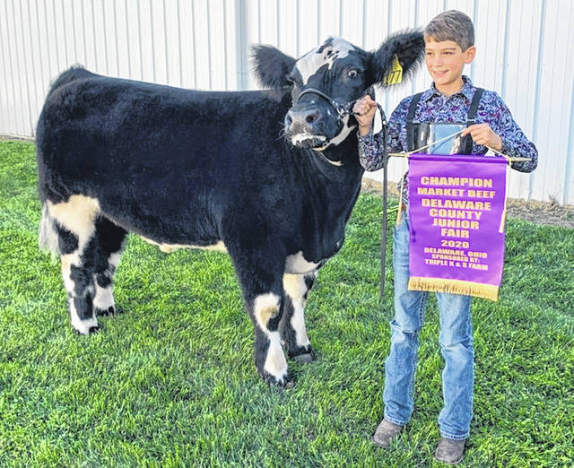 Pictured alongside his champion steer, Kase Tidd holds his Champion Market Beef banner.