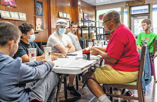 Richard Upton (red shirt), owner of J. Gumbo's in downtown Delaware, conducts a team meeting inside his restaurant at 9 N. Sandusky St.