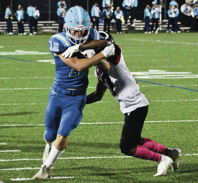 Olentangy Berlin's Ryan Horstman (12) fights for extra yardage against Whitehall's Taron Biles-Walker during Friday's playoff game in Delaware.