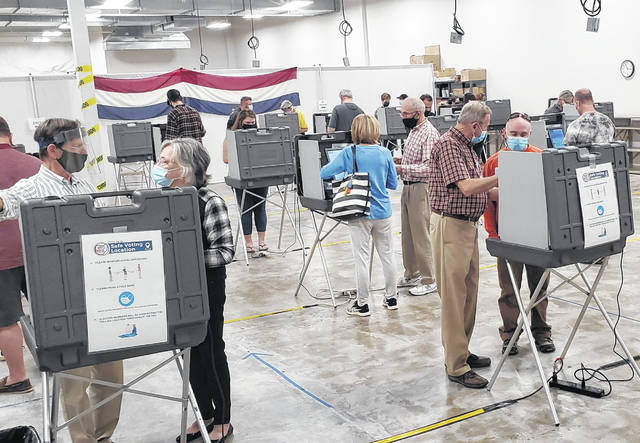 Volunteers assist voters with operating the voting machines during early in-person voting at the Delaware County Board of Elections Office at 2079 U.S. Route 23 N., Delaware.