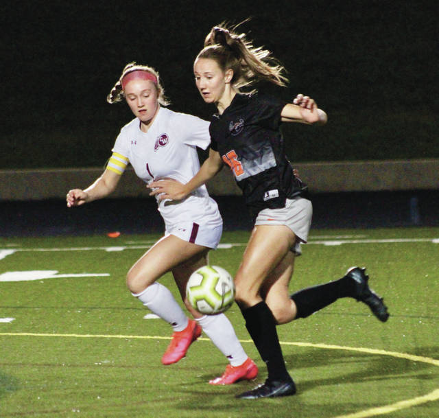 Delaware Hayes' Ava Bruns, right, beats a Canal Winchester defender to the ball during the first half of Tuesday's OCC showdown in Delaware.
