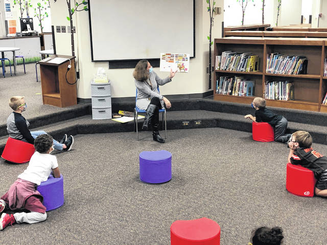 Robin Kress, a library media specialist at Conger Elementary School, reads a book to students during a visit to the library. Students and Kress wore masks throughout the lesson and maintained social distance to prevent the spread of COVID-19.