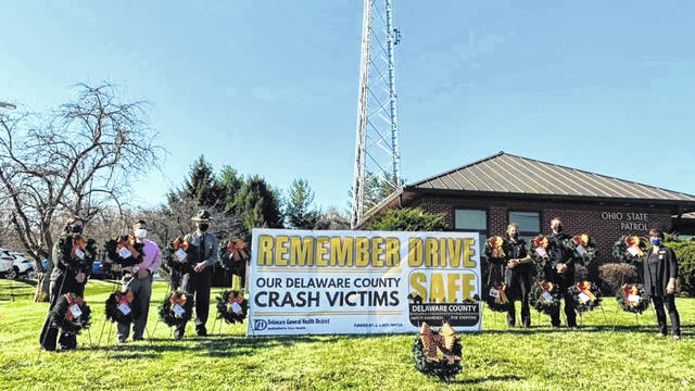 "Members of the SAFE Delaware County Coalition and law enforcement pose Thursday after the Remembrance Ceremony where wreaths were displayed by the Delaware Post of the Ohio State Highway Patrol on U.S. Route 23 to memorialize the 16 people who were killed in crashes this year. The event was organized by Jackie Bain (far right) and was moved up this year to coincide with the United Nations' ""World Day of Remembrance for Road Traffic Victims 2020,"" which is set for Sunday."