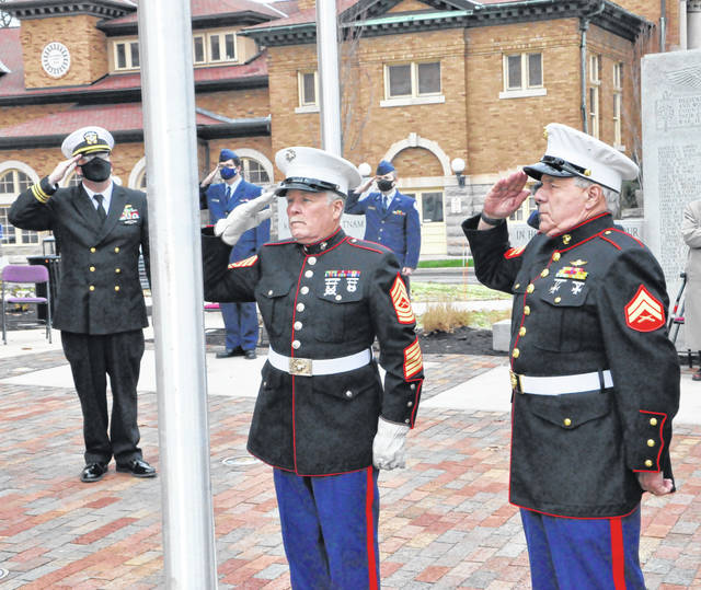 Local veterans of the United States Marine Corps salute following the raising of the USMC flag during Wednesday's ceremony.