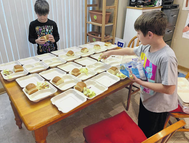 Alex and Nick Freihofner, students at Smith Elementary School, prepare meal kits as part of the school's monthlong generosity challenge.
