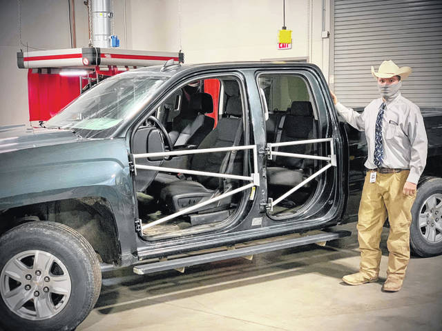 Blaize Foster, a senior in the DACC welding program, stands next to the truck doors he created for his senior capstone project.