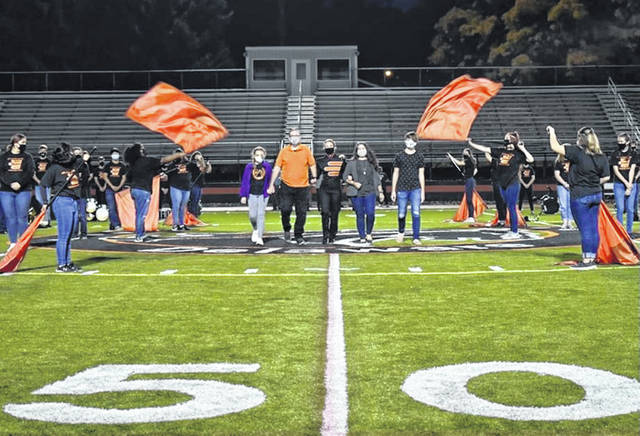 Senior Ainsley Tatman (center in uniform) walks down the field with her family during the Hayes High School Marching Band's senior night earlier this year.