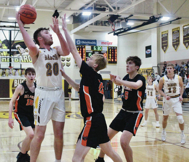Buckeye Valley's Troy Scowden (20) takes a shot over Delaware Hayes' Ryan Polter and Jacob Enke (5) during the first half of Saturday's non-league showdown in Delaware.