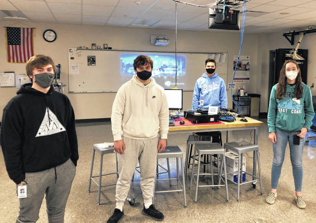 Cybersecurity students at the Delaware Area Career Center — Dillon Driskill, Matthew Weikel, Jordan Yonce and Taylor Quinn — stand next to equipment they've been developing and programming for the Delaware County Office of Homeland Security and Emergency Management's command center.