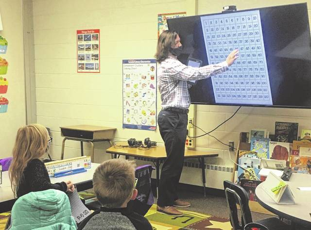 Noah Messerall teaches a class of first graders at Woodward Elementary School. Woodward and Dempsey Middle School were two of 31 schools that received the Purple Star Award this week from the Ohio Department of Education.
