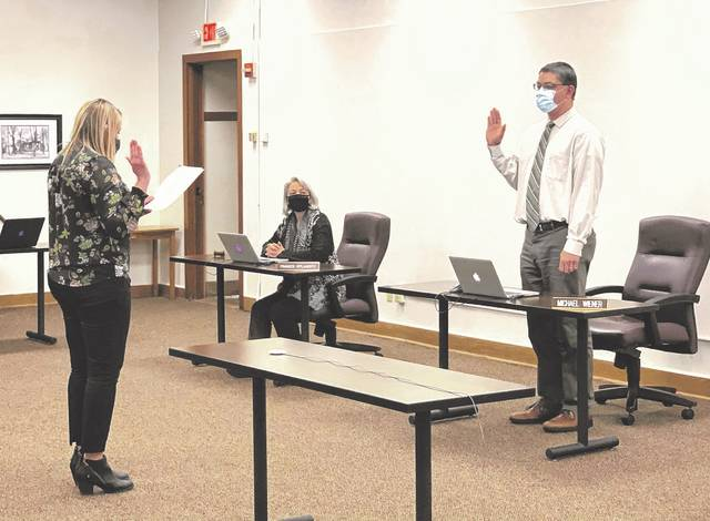 Delaware City Schools Treasurer and CFO Melissa Swearingen, left, administers the oath of office to DCS Board of Education member Michael Wiener after he was elected board vice president Monday. This is Wiener's first term as vice president since he joined the board in 2018. Frances O'Flaherty, middle, was elected board president Monday.