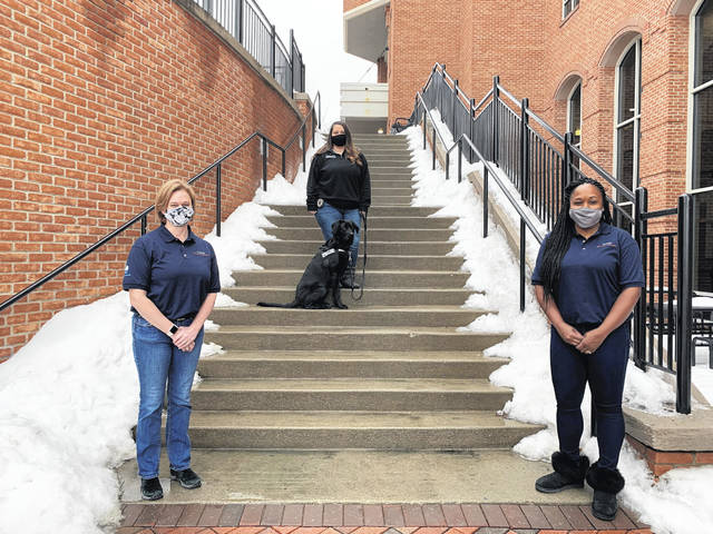 """Chief Probation Officer Kara Moore (left) and probation officers Gia DeGirolamo (middle with therapy dog, Franklin) and Megan Rivers (right) stand outside the Hayes Building Monday. The three officers attended """"Reimagining Juvenile Justice"""" training in 2020."""