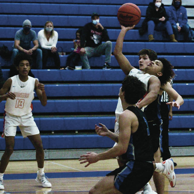 Olentangy Orange's Andre Irvin puts up a shot between a pair of Hilliard Bradley defenders during the first half of Friday's OCC showdown in Lewis Center.