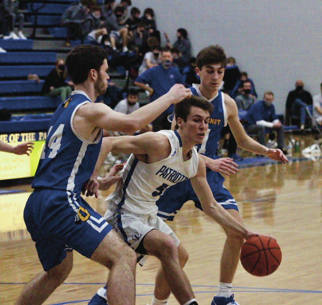Olentangy Liberty's Ty Foster, center, dribbles between Olentangy's Zack Wieging, left, and Luke Elmore during the first half of Saturday's non-league showdown in Powell.