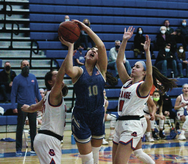 Olentangy Liberty's Taylor Redman puts up a shot between a pair of Olentangy Orange defenders during the first half of Tuesday's game in Lewis Center.