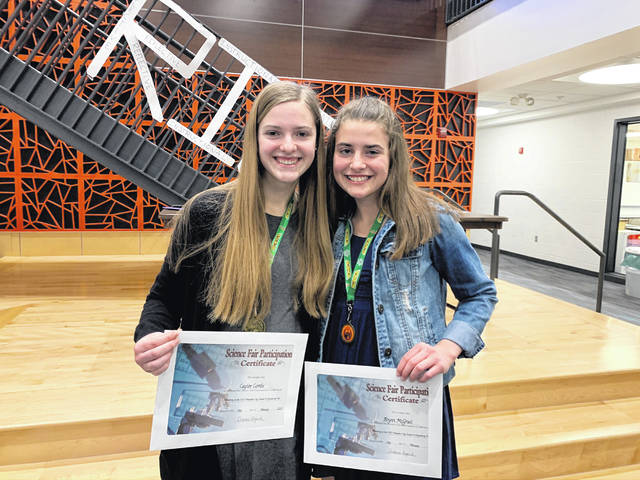 Caylee Combs, left, and Brynn McGrail pose together at Hayes High School after winning $1,000 scholarships from The Ohio Academy of Science's Believe in Ohio program. Over the past four years, the pair have been working on a project to use duckweed as a natural fertilizer to prevent runoff pollution.