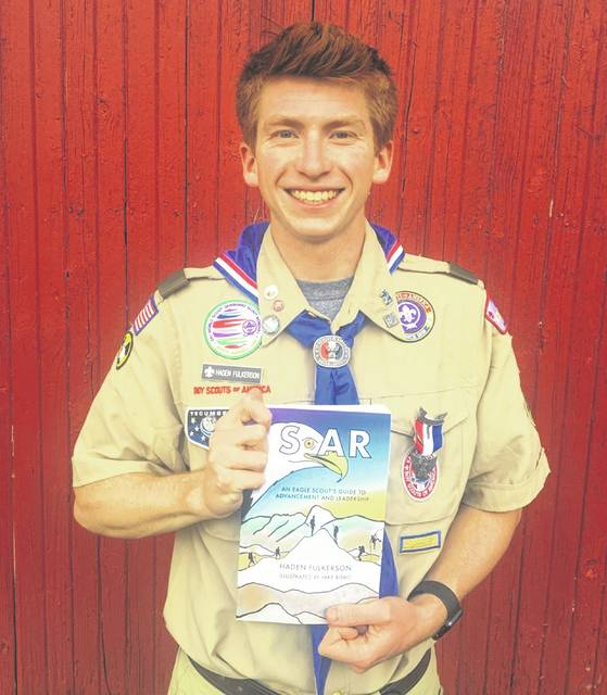 """Eagle Scout Haden Fulkerson, a Genoa Township resident, holds the book he recently published titled """"SOAR: An Eagle Scout's Guide to Advancement and Leadership."""""""