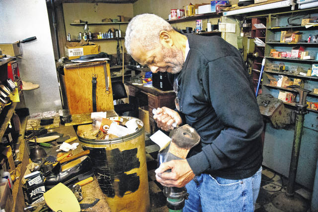 In this file photo from April 2019, Cobbler Ralph Martin, who passed away Sunday, cuts the stitching on the sole of a shoe, preparing the sole to be removed and replaced with a new one. Martin worked in the same shop at 28 W. Winter St. in downtown Delaware for 60 years.