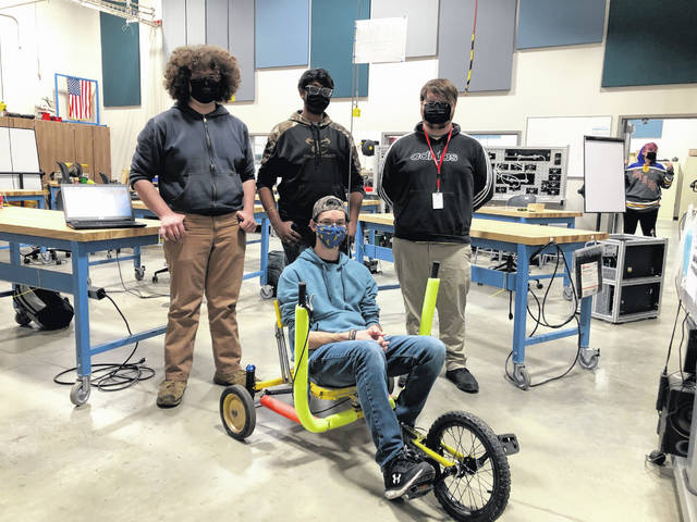 Engineering technology seniors on one of the teams participating in the adult tricycle design project pose for a photo with their tricycle that they researched, designed and built. Timothy Kolva sits in the seat. He's surrounded by his teammates (left to right): Evan McDonald, Tarun Subbarayalu and John Simonis.