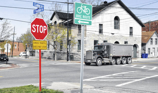 """City of Delaware workers on Tuesday removed the overhead flasher at the intersection of East Winter and Lake streets. Pictured is one of the new flashing LED stop signs installed in place of the traffic signal on East Winter Street along with placards below the signs warning drivers that """"Cross Traffic Does Not Stop."""""""