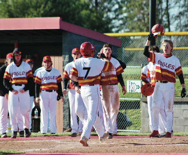 Big Walnut's Colin Pierce (7) is greeted by his teammates after hitting a three-run homer in the third inning of Friday's non-league showdown against visiting Buckeye Valley.