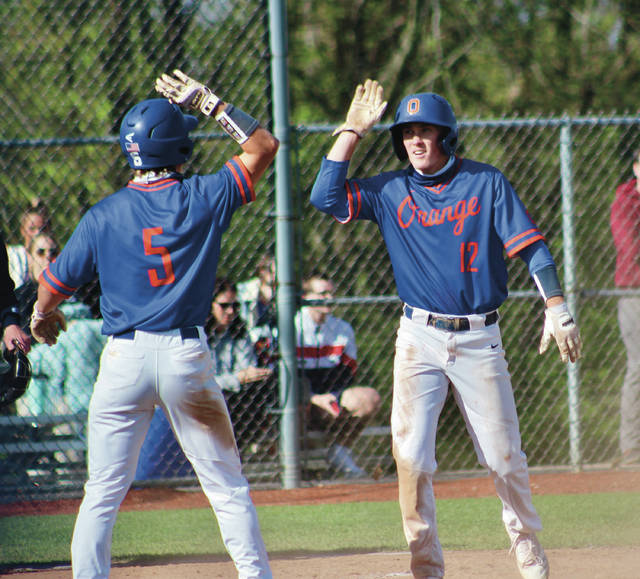 Olentangy Orange's Caden Konczak (5) and Josh Laisure (12) celebrate after scoring on a single by Logan Shearer during the first inning of Friday's game against visiting Olentangy Liberty.