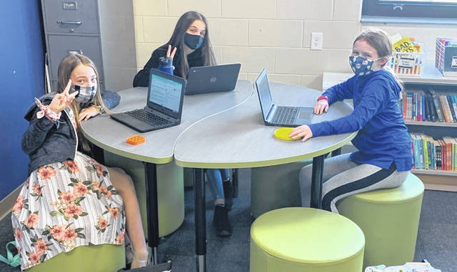 Cohort A fifth graders Madison Gray, Khloe White and Natalie Bledsoe pose for a photo while working Tuesday in one of the new classrooms at Schultz.
