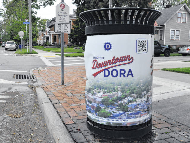 """Trash cans throughout downtown Delaware like the one at the corner of West Winter and North Franklin streets now feature """"Enjoy the Downtown DORA"""" banners, while signs like the one to the left of the trash receptacle remind the public that alcoholic beverages are not permitted outside the DORA boundaries."""
