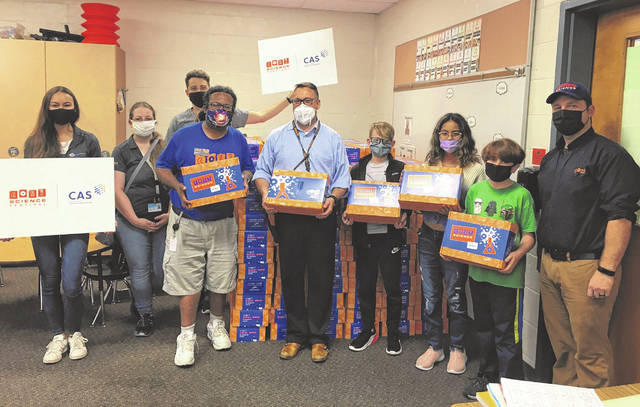 Representatives from COSI and CAS, a division of the American Chemical Society, present 500 science kits to Woodward Elementary School Principal Eric Barr (middle in light blue) and students at Woodward on Tuesday.