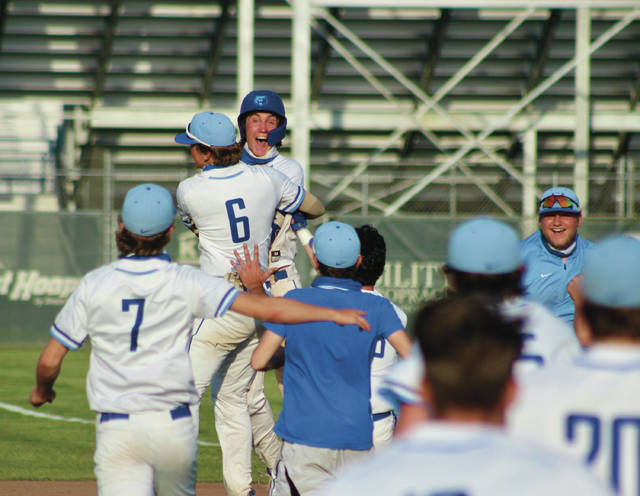 Olentangy Berlin's Jake Kinkead, wrapped in a bear hug from Harrison Brewster (6), celebrates with his teammates after hitting a walk-off single in the bottom of the ninth inning of Tuesday's Division I district semifinal against visiting Pickerington North.